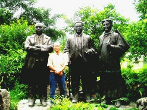 Writer standing among three statues of China's important figures