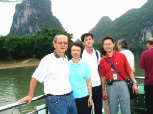 Writer in white T-shirt, his wife and son, and tour-guide in red shirt on a cruise boat