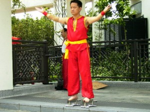A performer standing on sharp knives with his bare feet