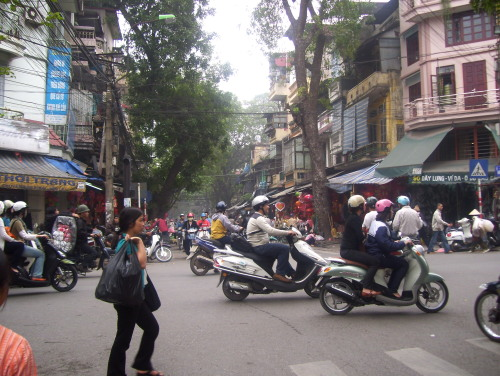 An Old Quarter street lined with quaint shophouses and trees