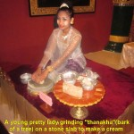 "A pretty girl grinding ""thanakha"" bark on a stone-slab"