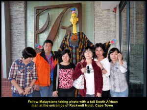 Some fellow-Malaysians taking photo with the tall, yellow man