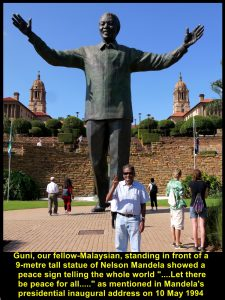 Guni, fellow-Malaysian, standing with a V-sign in front of a 9-metre tall statue of Nelson Mandela, Union Buildings, Pretoria