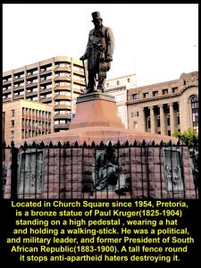 Statue of Paul Kruger holding a walking-stick and wearing a hat on a high plinth at the centre of Church Square