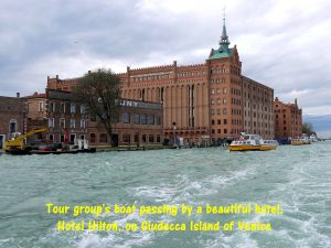 Tour group's boat passing by a beautiful building, Hotel Hilton, on Giudecca Island of Venice