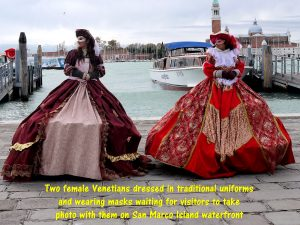 Venetian ladies in traditional costumes and wearing masks on waterfront