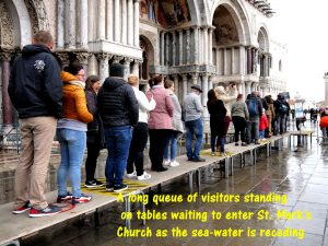 Visitors standing on tables to prevent their feet from getting wet in flooded San Marco Square, Venice