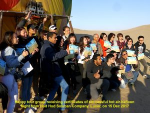 Happy tour group receiving certificates of successful hot air-balloon flight in Luxor