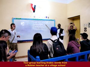 A Nubian teacher teaching tour group some Arabic words at a village school