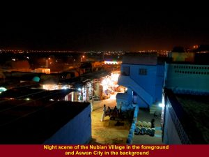 Night scene of Nubian village in the foreground and Aswan city in the background