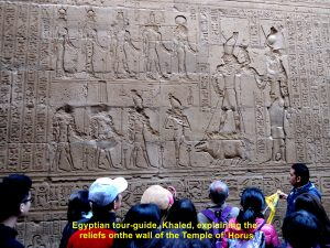 Tour guide, Khaled, explaining the relief on a wall of Temple Horus, Edfu