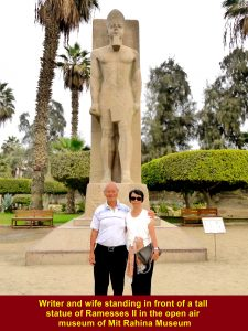 Writer and wife standing in front of a tall statue of Ramesses II in the open museum of Mit Rahina Museum