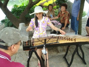 "A pretty lady playing ""guzheng"" by Xishan Lake, Quilin City"