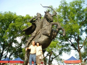 Writer and his wife posing with a large equestrian statue by Bayan Lake, Quilin City