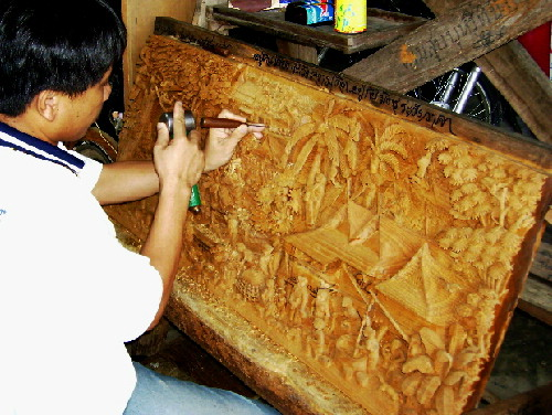 A wood-carver painstakingly carving a 3 D-picture