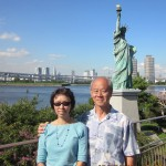A smaller replica of Statue of Liberty behind writer and wife