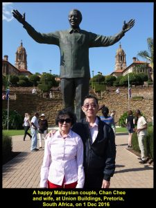 Chan Chee and wife, fellow-Malaysians, standing in front of the tall statue of Nelson Mandela