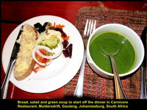 A bowl of green-coloured soup and a plate of bread and salad were first served.