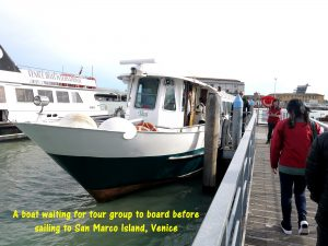 Tour group taking a boat to San Marco Island of Venice