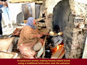 A worker making freshly baked bread in a traditional oven for guests' lunch
