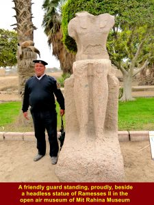 A friendly guard standing, proudly, next to a headless statue of Ramesses II in the open air museum of Mit Rahina Museum