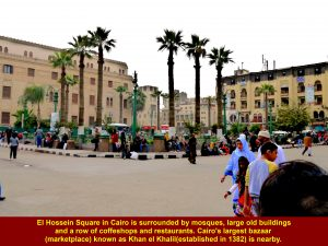 El Hossein Square is surrounded by El Hossein Mosque, a row of of coffee shops and restaurants, and large, old buildings.